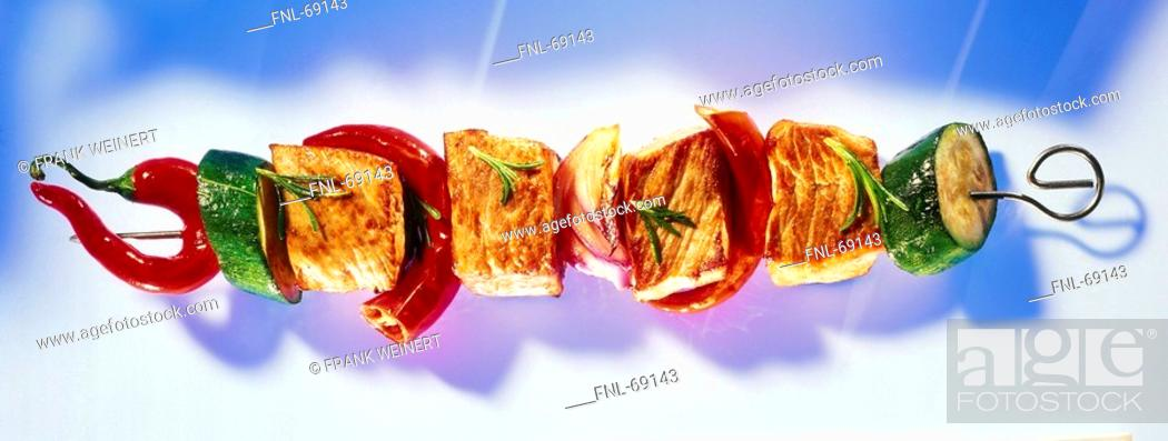 Stock Photo: Cubes of meat and red chilli peppers with slices of cucumbers on skewer.