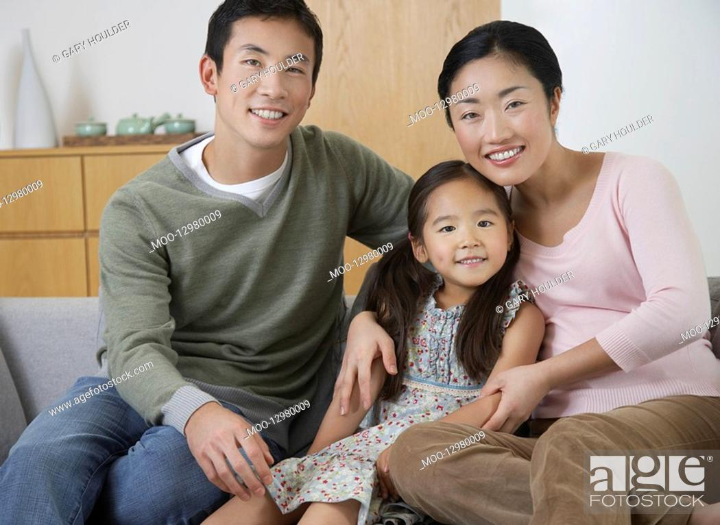 Stock Photo: Young couple and daughter Posing on Sofa.