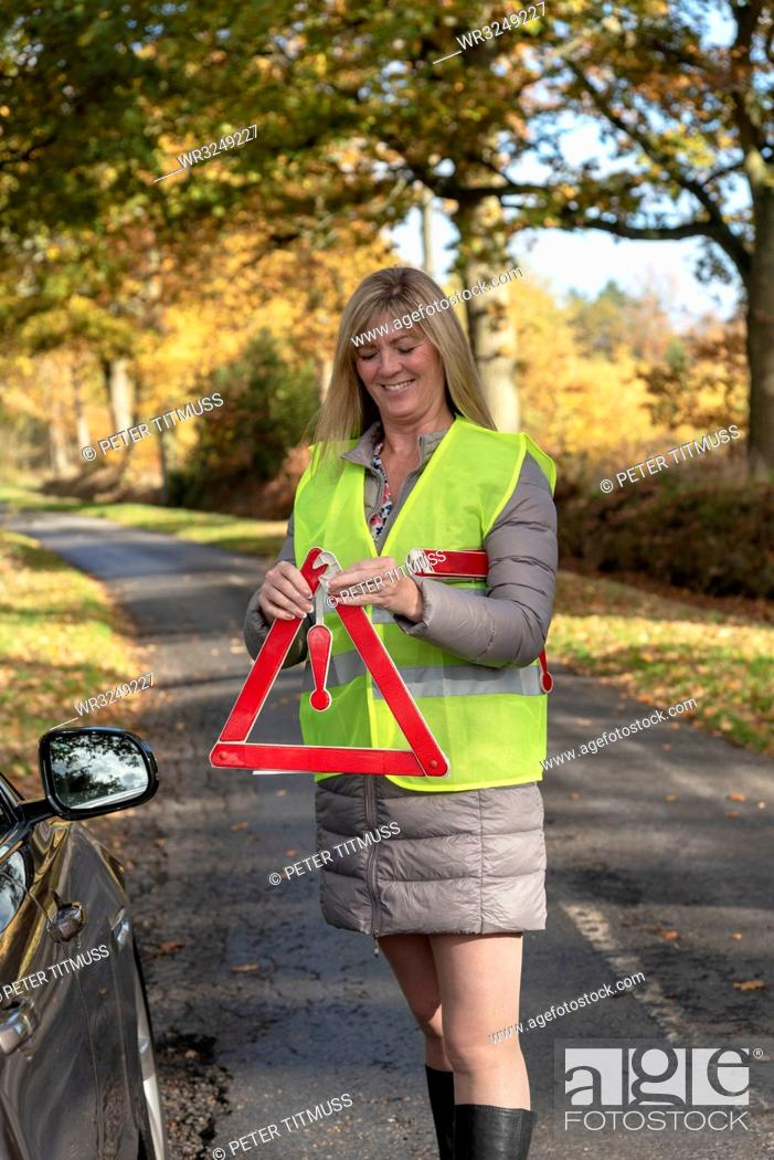 Stock Photo: Female motorist putting out a reflective safety triangle following a roadside breakdown.