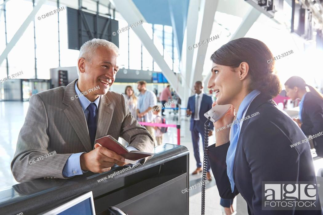 Stock Photo: Customer service representative helping businessman with passport at airport check-in counter.