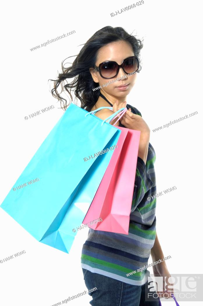 Stock Photo: Woman carrying shopping bags and smirking.