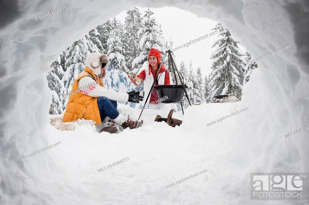 Stock Photo: Austria, Salzburg, Young women sitting at fire place in winter.