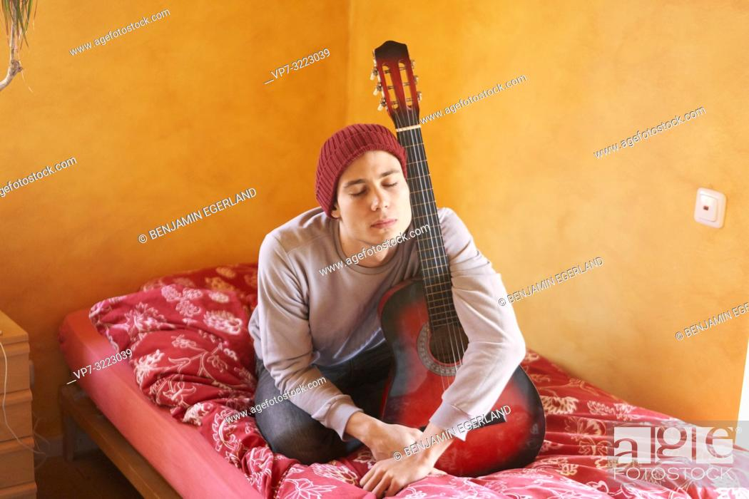 Stock Photo: young man with guitar sitting on bed at home, closed eyes, tired, pensive emotion, in Waakirchen, Bavaria, Germany.
