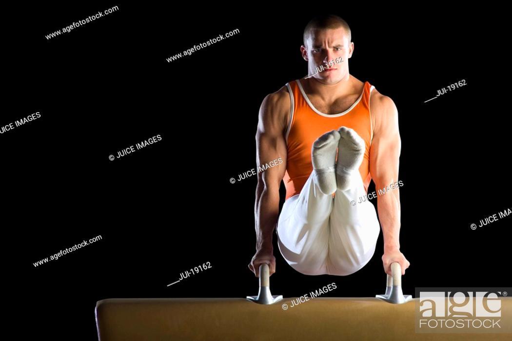 Stock Photo: Male gymnast performing on pommel horse, portrait.