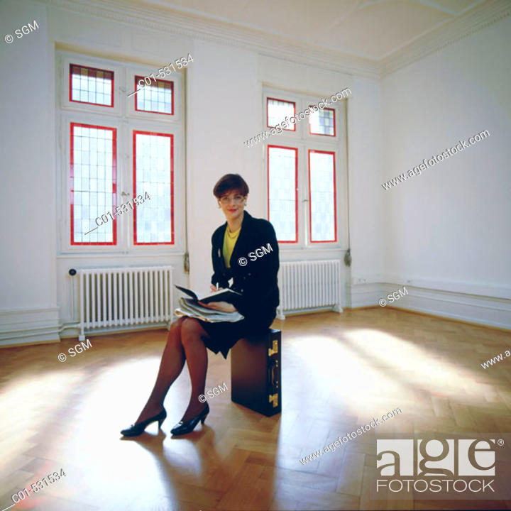 Photo de stock: Young businesswoman with black dress sitting in empty room.