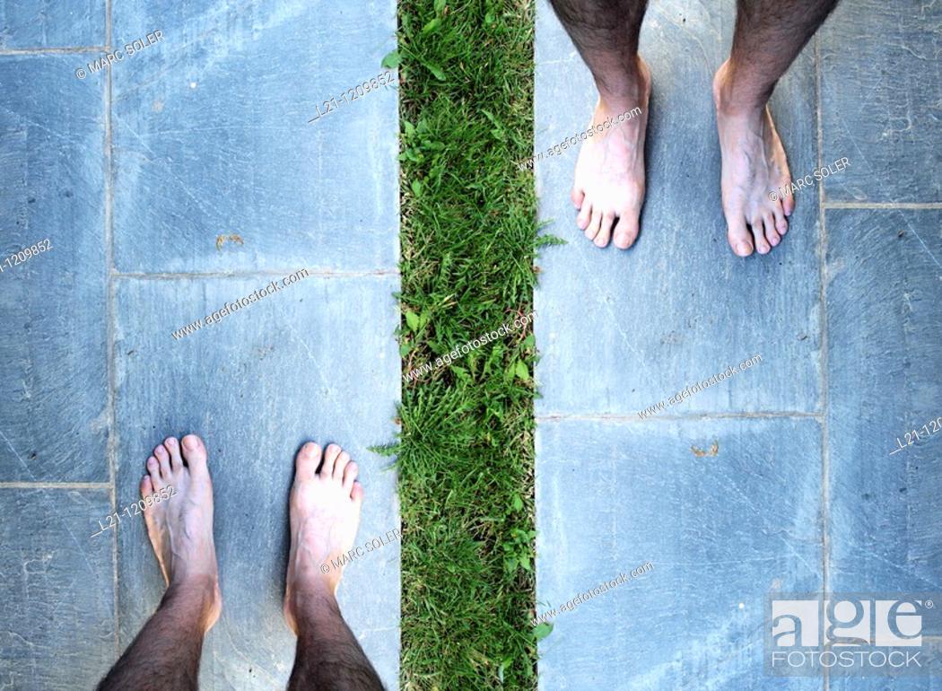 Stock Photo: Man's bare feet on brick slate.