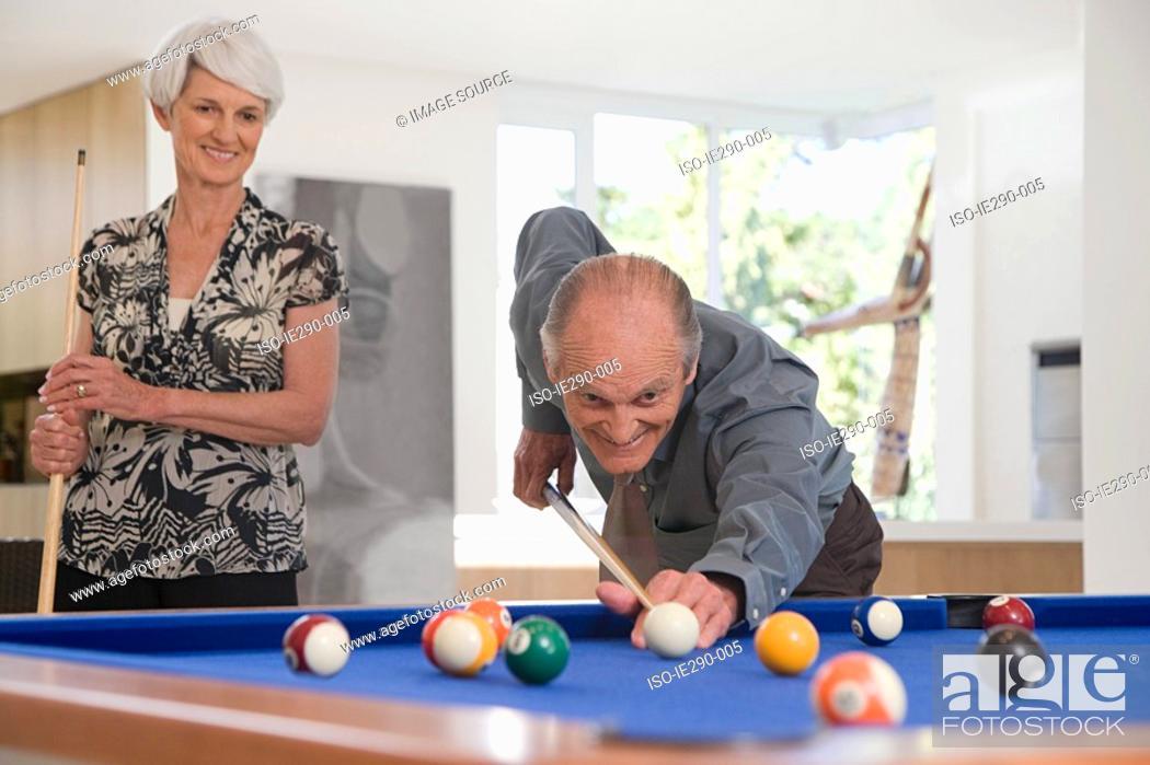 Stock Photo: A senior couple playing pool.