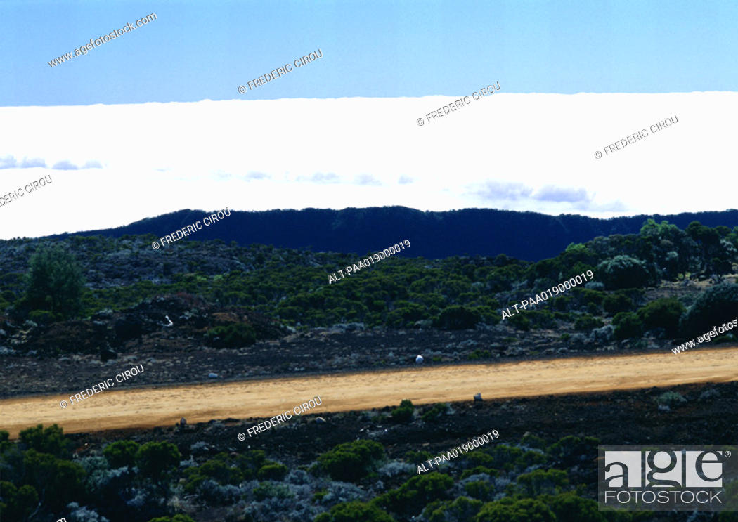 Stock Photo: Mountain road with clouds behind mountain.
