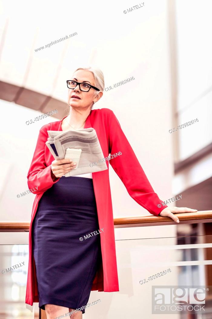 Stock Photo: Businesswoman reading newspaper on office balcony.