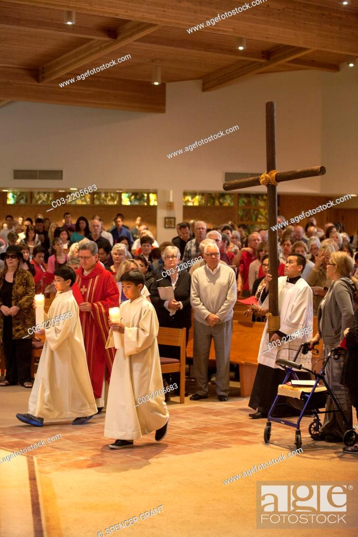Stock Photo: The congregation watches as young robed altar servers carry candles as they lead a procession carrying a cross on Holy Thursday at St.