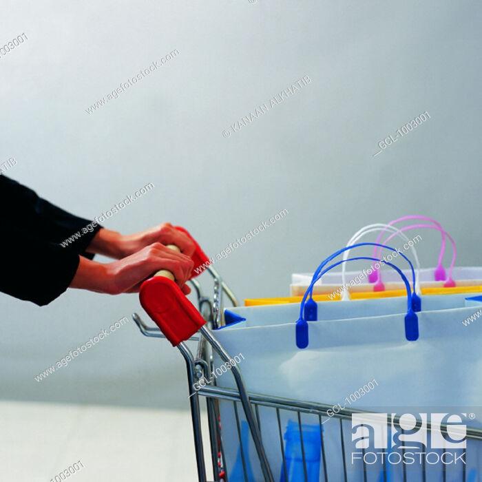 Stock Photo: Arab woman pushing a shopping trolley.