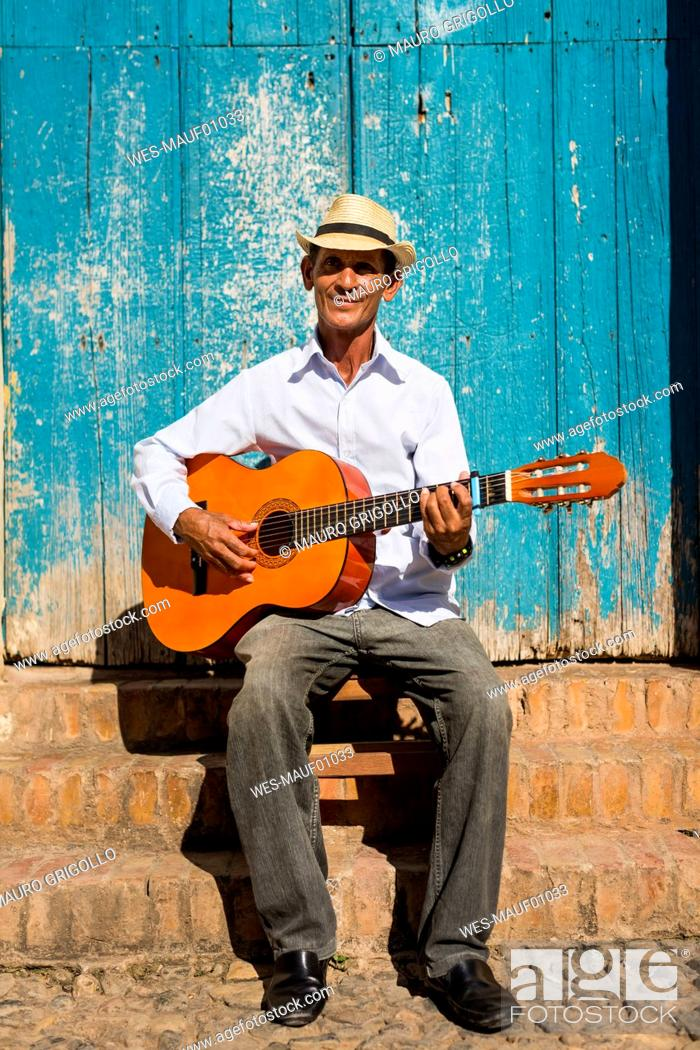 Imagen: Cuba, portrait of man playing guitar on the street.