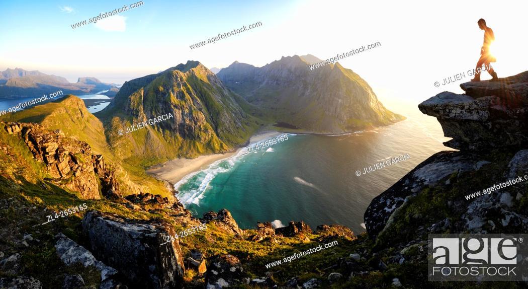 Stock Photo: Norway, Nordland, Lofoten islands, Moskenesoy island, hiker at the summit of mount Ryten (543m), the isolated beach of Kvalvika below.