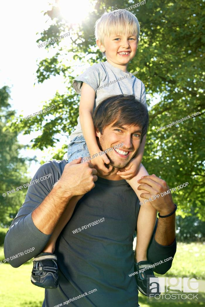 Stock Photo: Germany, Cologne, Father carrying son on shoulders, smiling, portrait.