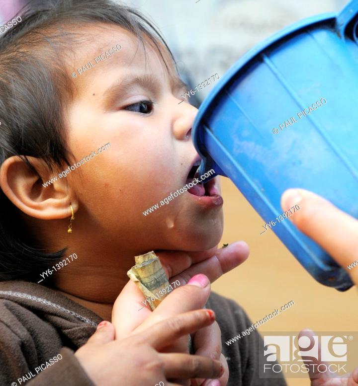 Stock Photo: little girl drinking water during festival, the nepalis , life in kathmandu , kathmandu street life , Nepal.
