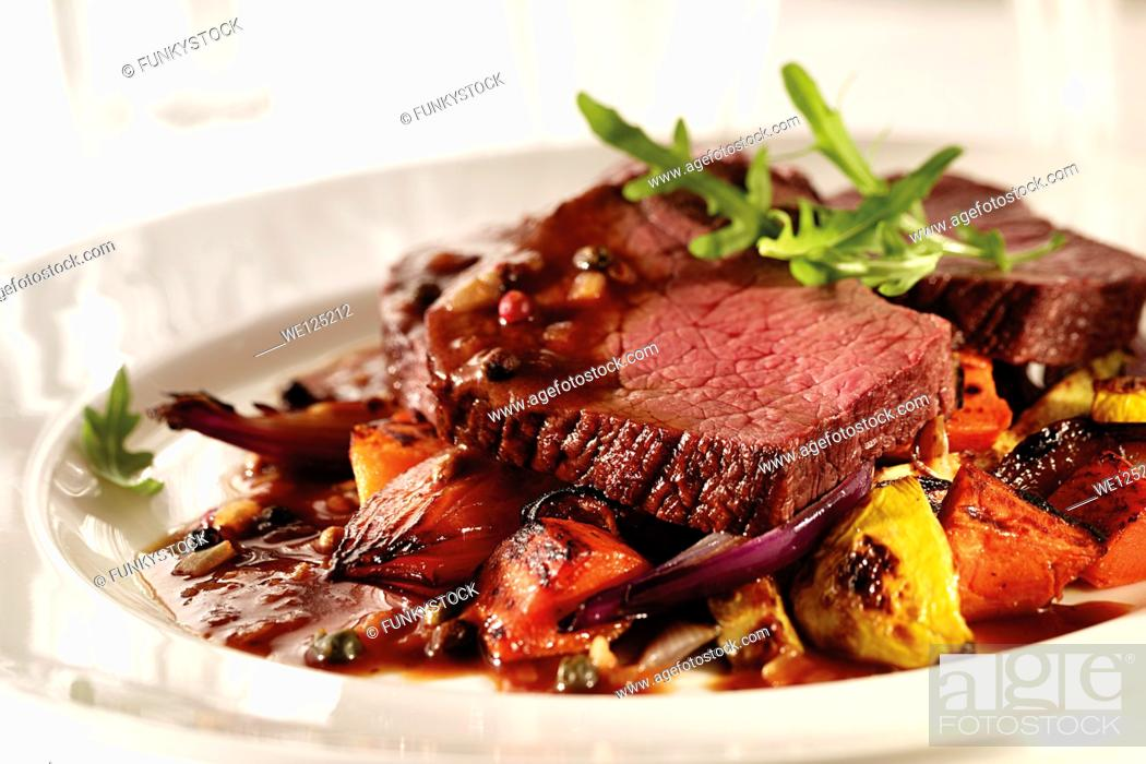 Stock Photo: Fillet steak slices on a bed of roasted vegetables with gravy.