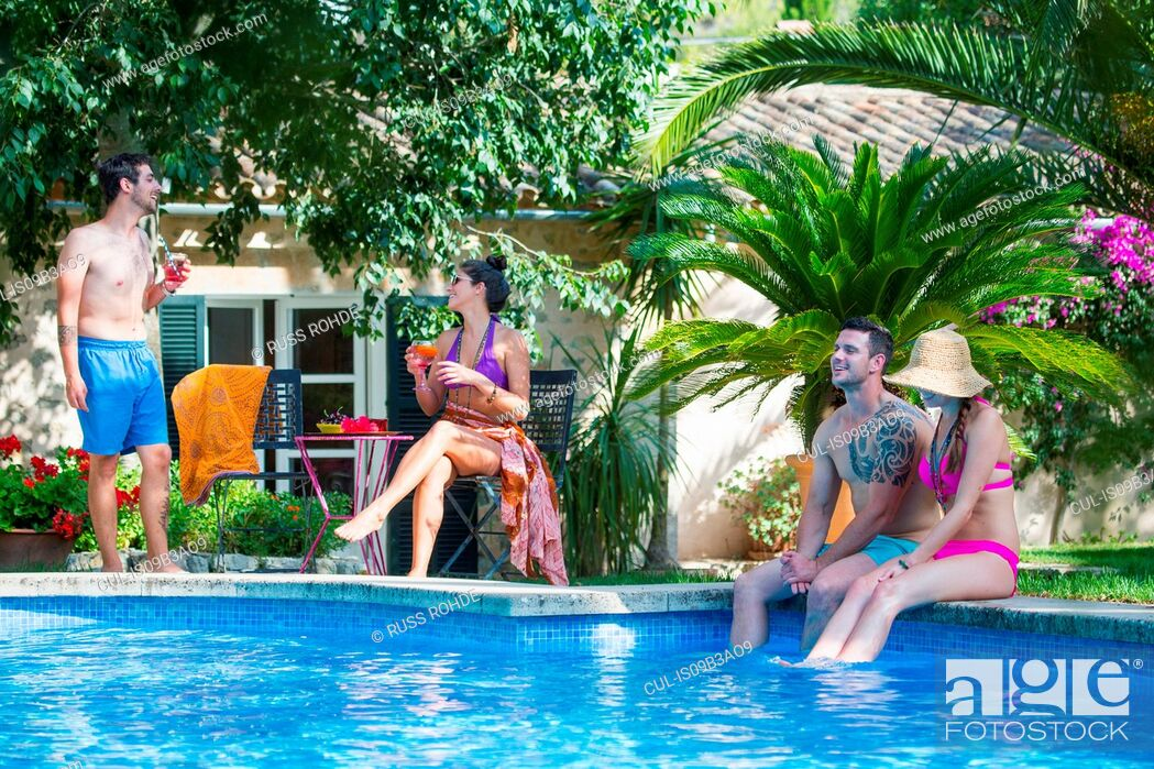 Stock Photo: Friends sitting on poolside.