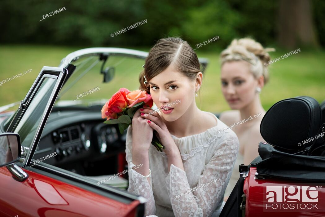 Stock Photo: Bride with bouquet of roses in red convertable car.