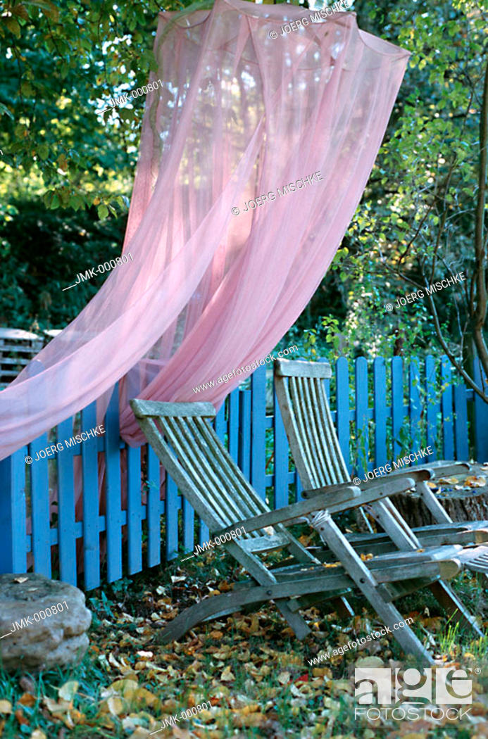 Stock Photo: Deckchairs and a mosquito net in an autumnal garden.