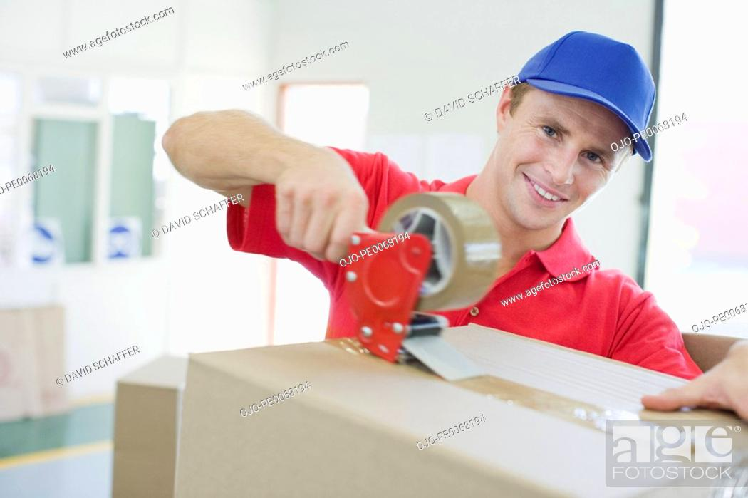 Stock Photo: Delivery man taping cardboard box in warehouse.