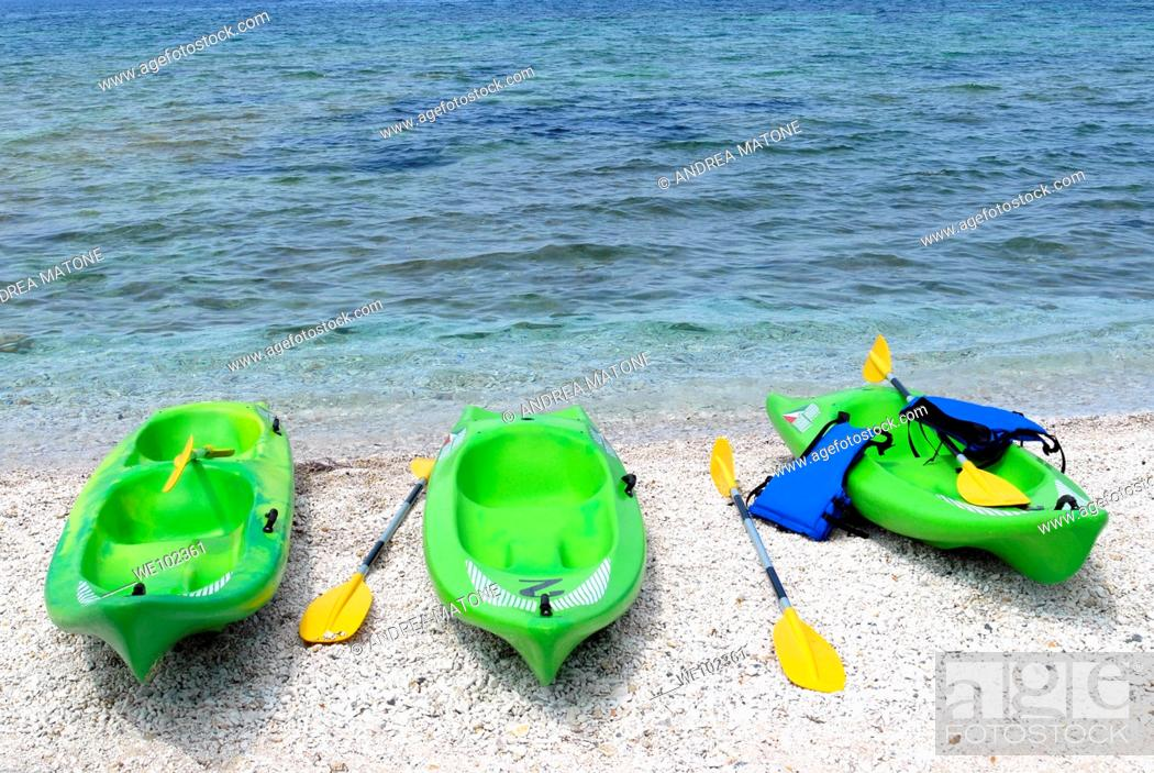 Stock Photo: Three green kayaks on beach Capo Bianco Isola d'Elba Tuscany Italy.