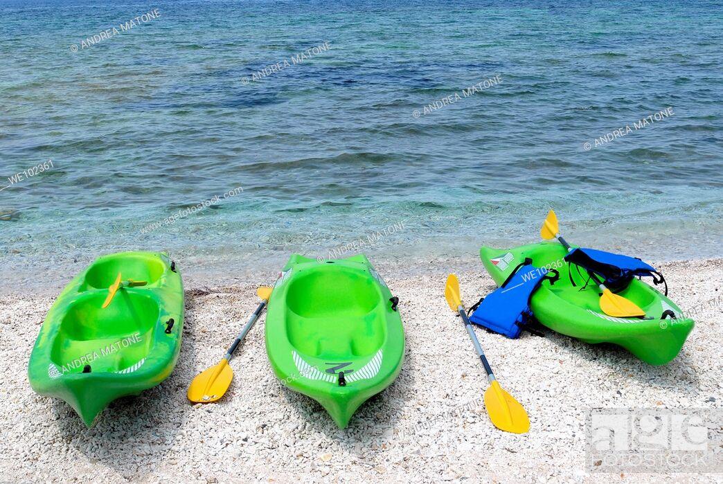 Stock Photo: Three green kayaks on beach Capo Bianco Isola d'Elba Tuscany Italy.
