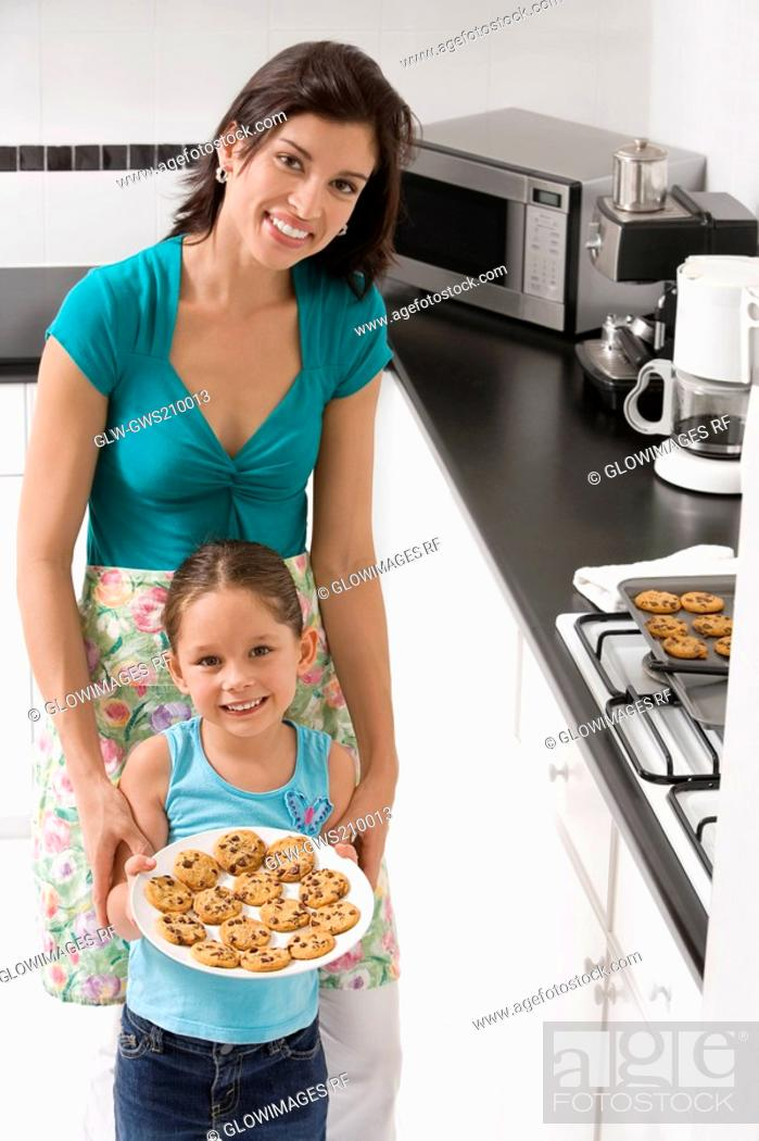 Stock Photo: Young woman with her daughter holding a plate of cookies in the kitchen.