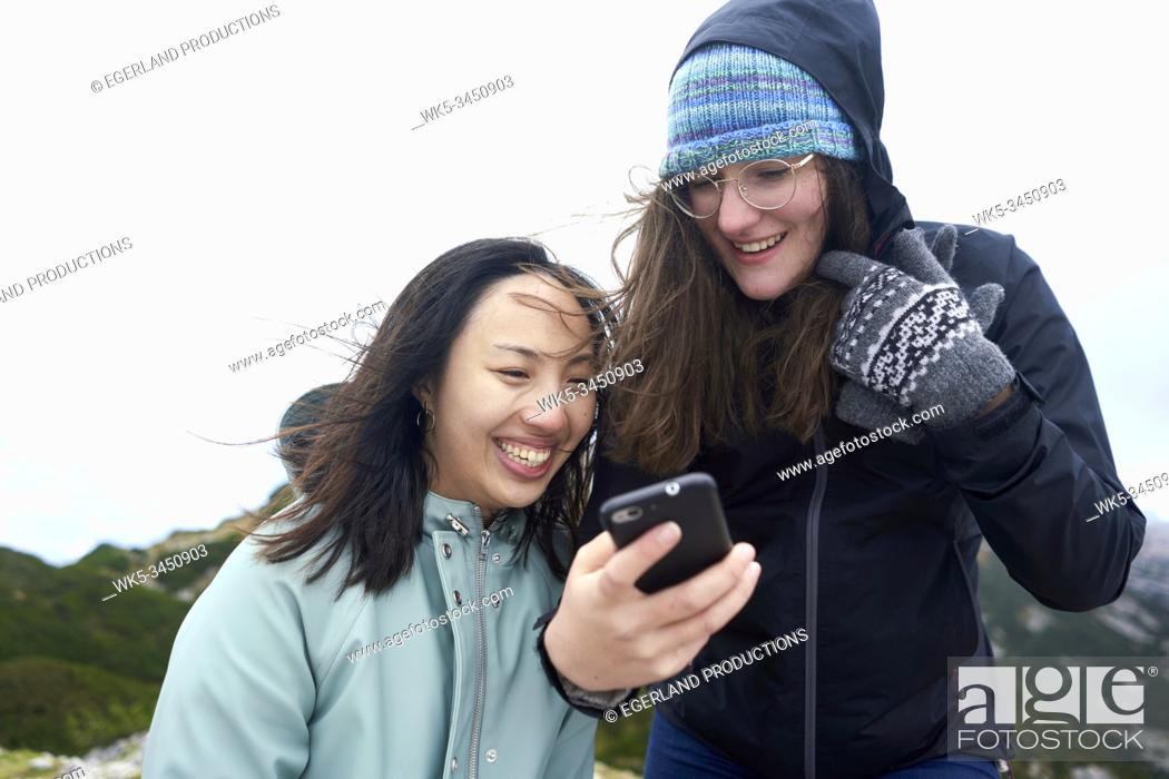 Stock Photo: friends looking at smartphone during hiking trip.