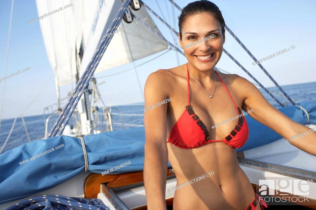 Stock Photo: Hispanic woman in bikini on sailboat.
