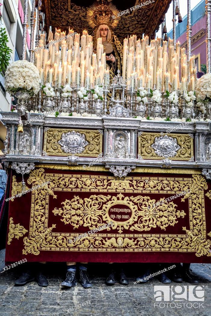 Imagen: Paso of the virgin Mary being carried through the streets of Seville. The feet of the costaleros stick out underneath the image.