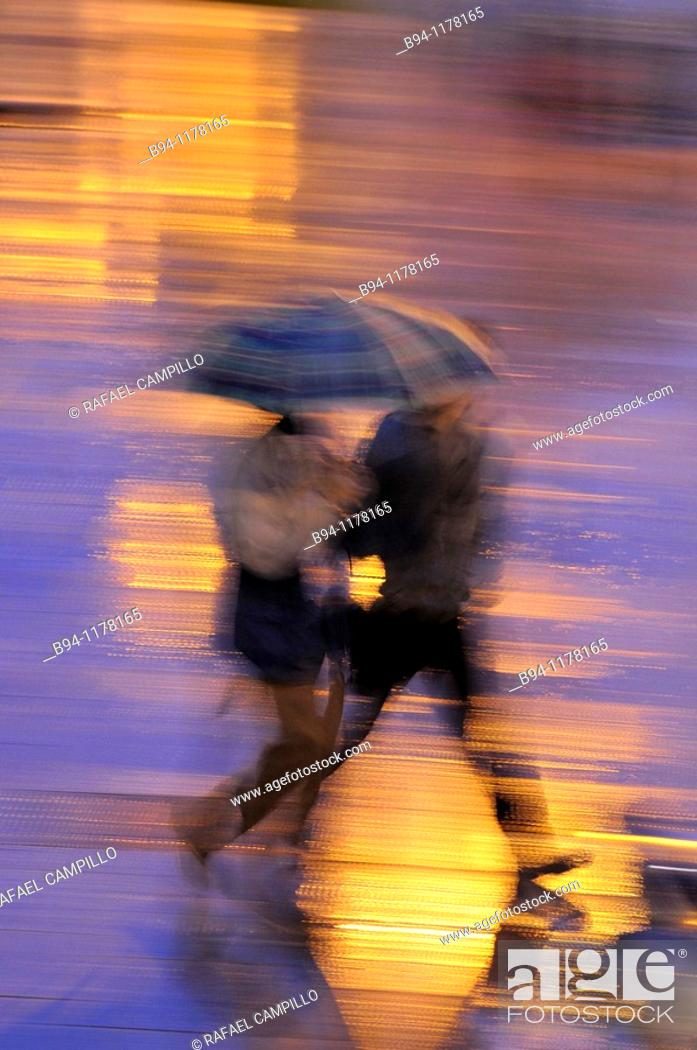 Stock Photo: People with umbrellas in a rainy day, Barcelona, Catalonia, Spain.