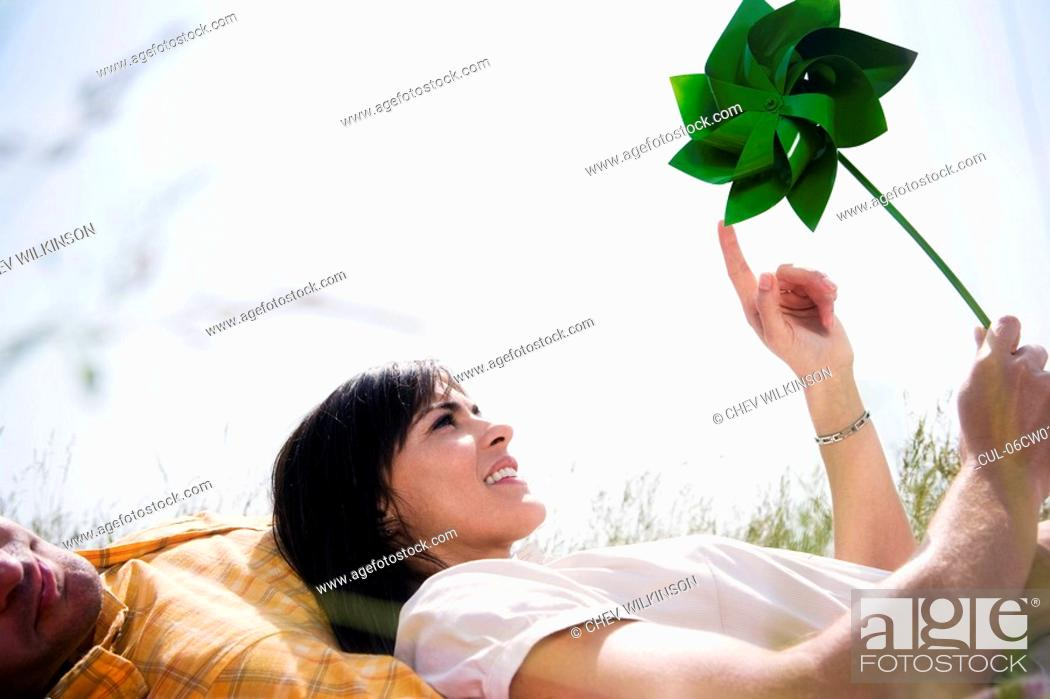 Stock Photo: Woman in grass with windmill.