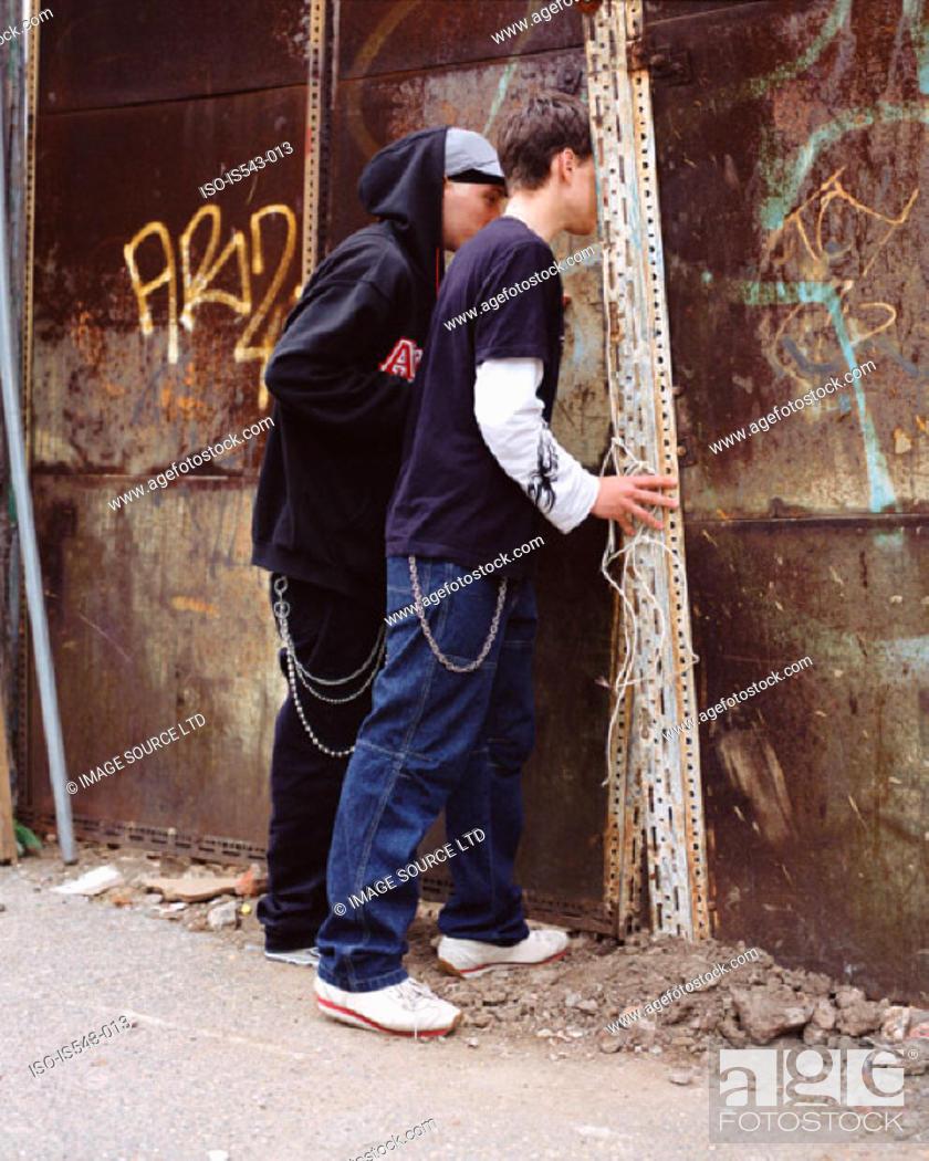Stock Photo: Teenage boys peering through wall.