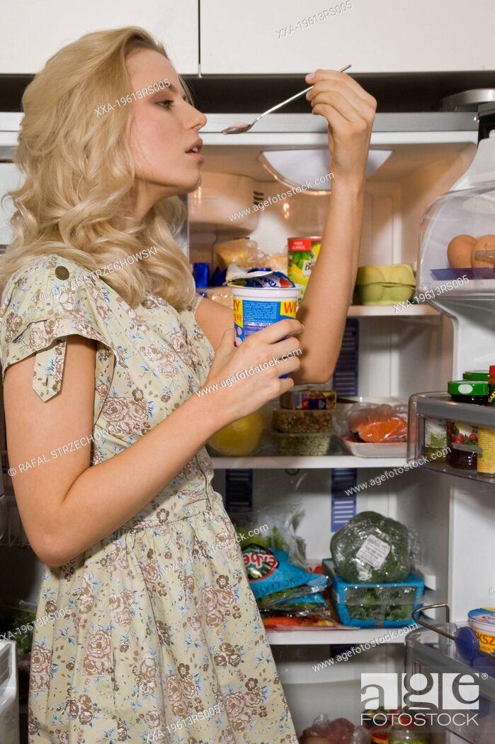 Imagen: woman eating yogurt next to refrigerator.