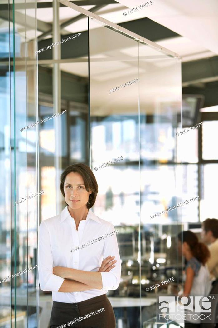 Stock Photo: Businesswoman standing in office front view.