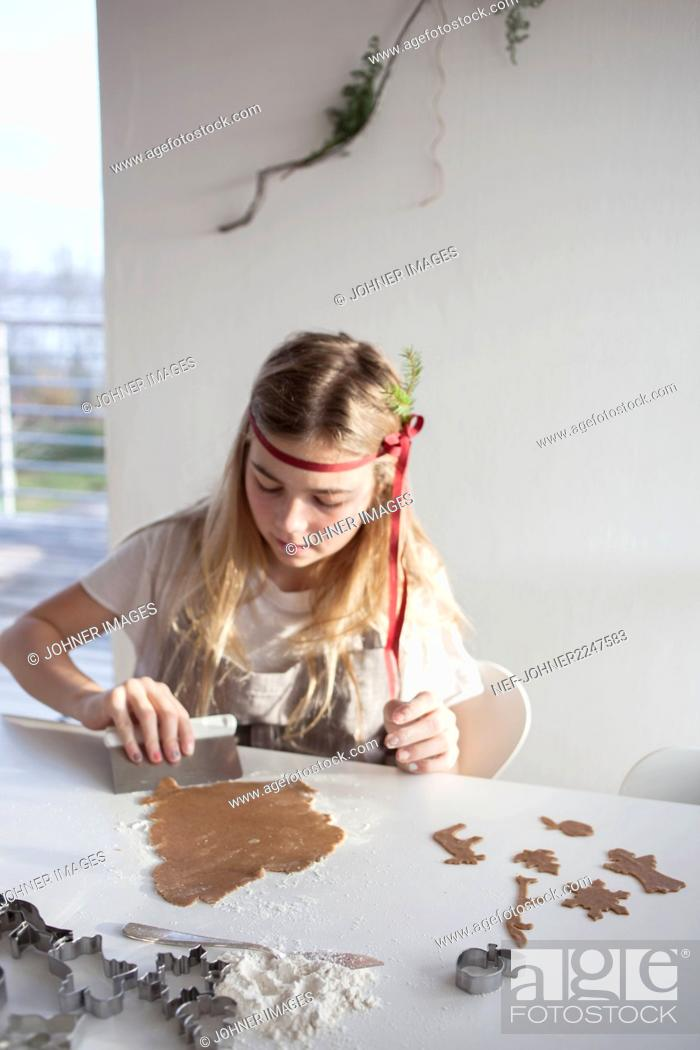 Stock Photo: Girl making gingerbread cookies.