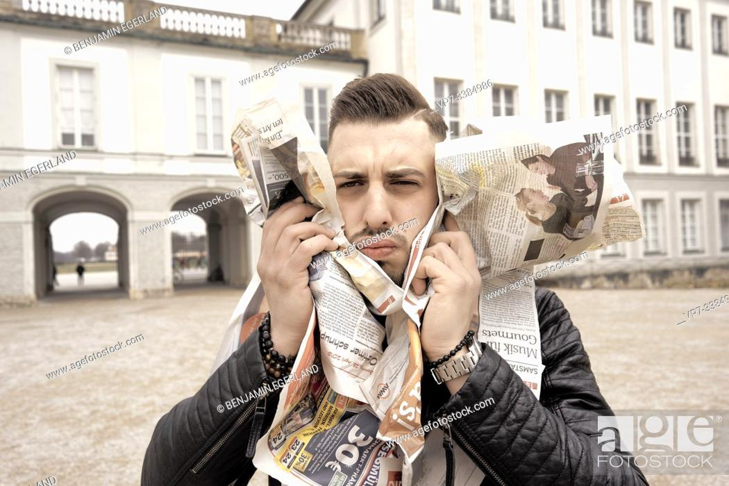 Stock Photo: Man assailed by newspapers, in Munich, Germany.