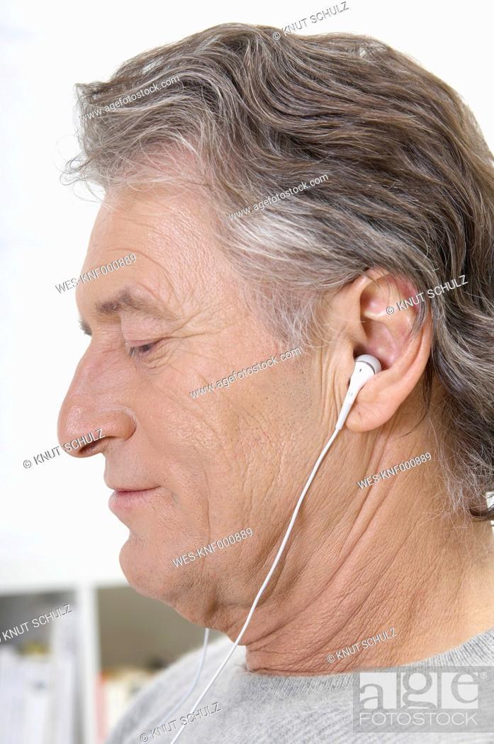 Stock Photo: Germany, Hamburg, Senior man listening music, close up.