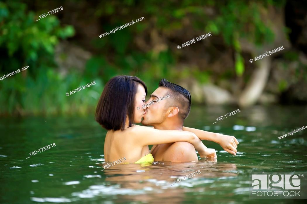 Stock Photo: Young couple in love - Asian woman, 20 years old, Korean Ethnicity, hispanic man, 22 years old, location Frio River near Leakey, Texas, USA.