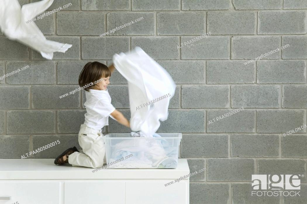 Stock Photo: Little boy playing with laundry, smiling, side view.