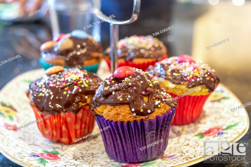 Stock Photo: Chocolate covered cupcakes, with sprinkles on top.