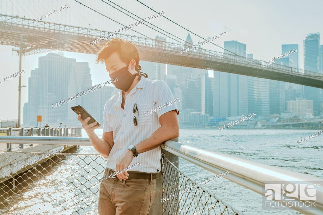Stock Photo: Young man by river wearing face mask with phone.