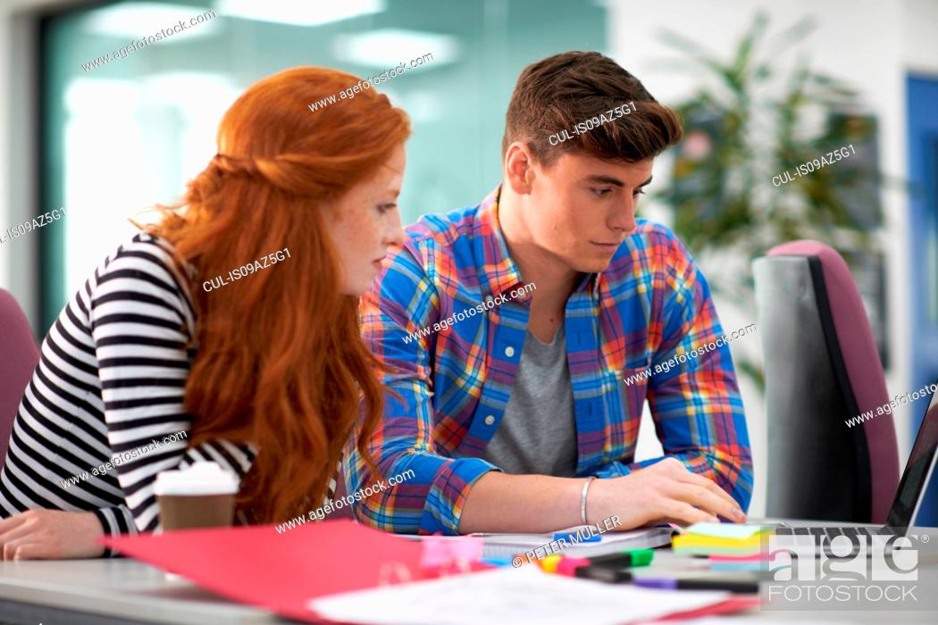 Stock Photo: Young female and male college students looking at laptop on desk.
