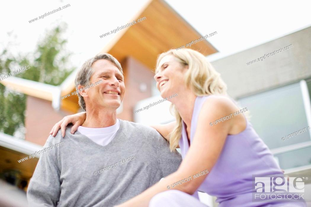 Stock Photo: Couple hugging and laughing on deck of modern house.