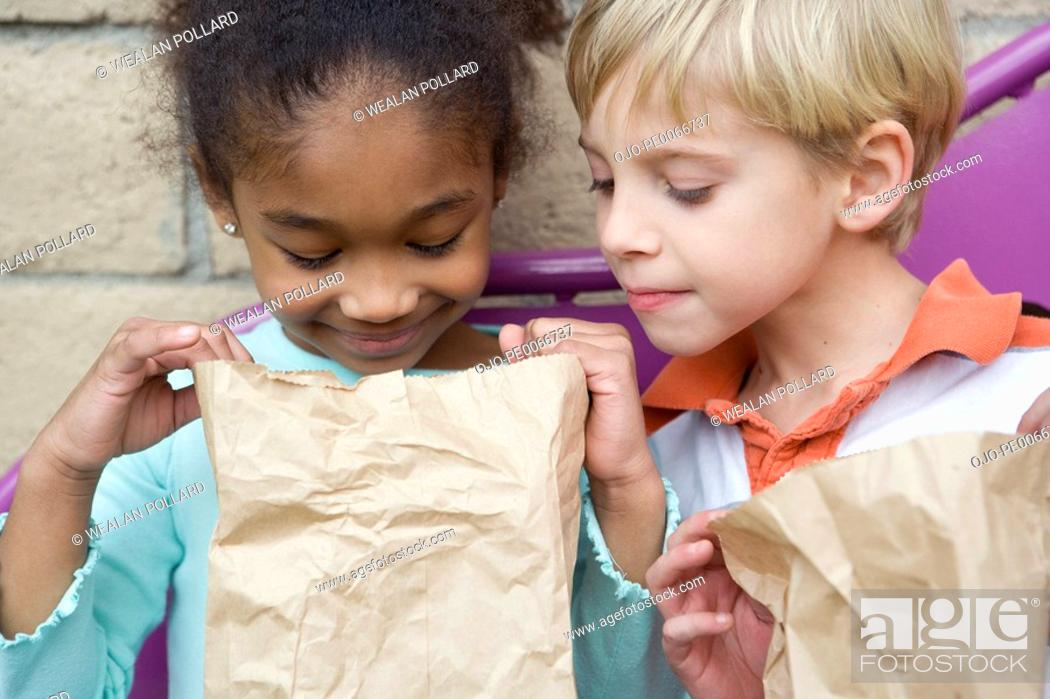 Stock Photo: Boy looking in friend's lunch bag at recess.