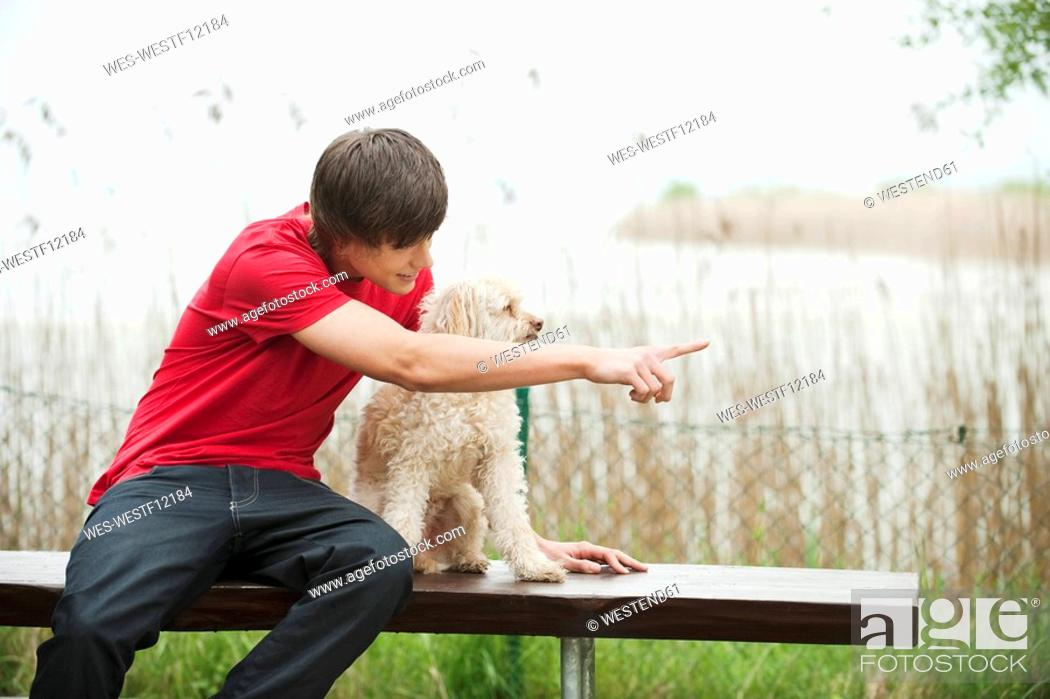 Stock Photo: Germany, Bavaria, Ammersee, Young man and dog on bench, portrait.
