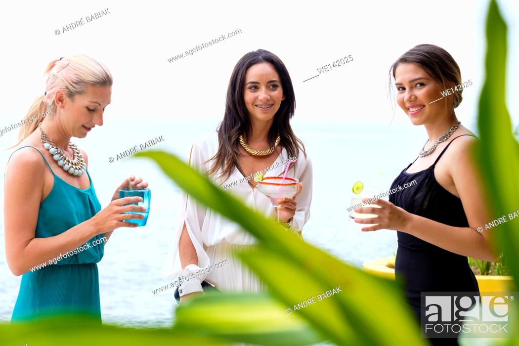 Stock Photo: Three young attractive women in elegant dresses enjoying an outdoor cocktail party in Puerto Vallarta, Mexico.