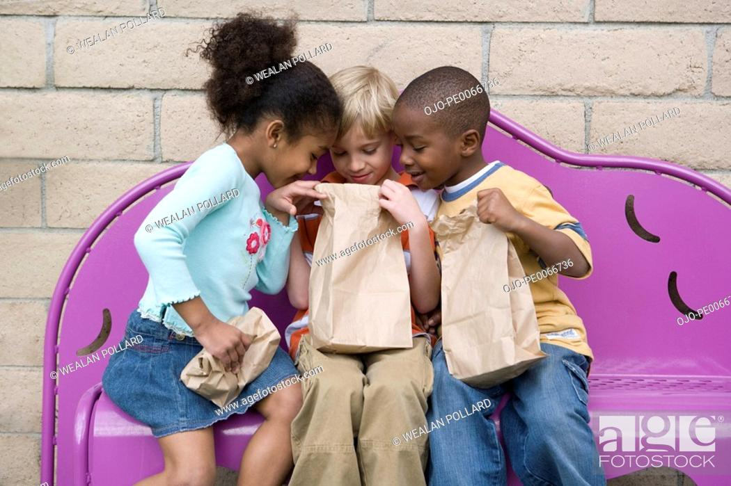 Stock Photo: Children looking in friend's lunch bag at recess.