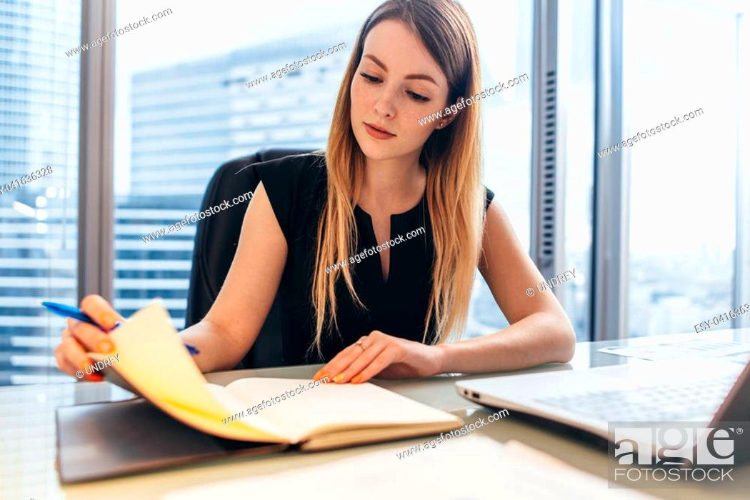 Stock Photo: Confident female entrepreneur planning her workday sitting at her desk holding pen thinking looking at notebook in office.