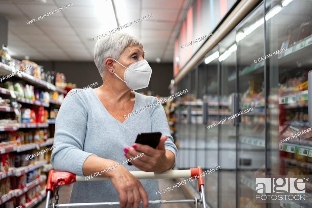 Stock Photo: Caucasian senior woman with face mask and telephon shop in supermarket.